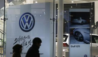 FILE - In this Thursday, Nov. 26, 2015, file photo, people walk by a Volkswagen logo at a dealership in Seoul, South Korea. Volkswagen will spend more than $15 billion to settle consumer lawsuits and government allegations that it cheated on emissions tests in what lawyers are calling the largest auto-related class-action settlement in U.S. history. The settlement was revealed Tuesday, June 28, 2016, by a U.S. District Court in San Francisco. (AP Photo/Ahn Young-joon, File)