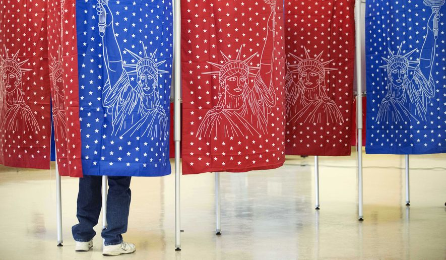A voter marks a ballot for the New Hampshire primary inside a voting booth on Feb. 9 in Manchester, N.H. (Associated Press)
