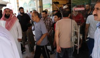 In this Sunday, June 19, 2016 photo, men wait outside the al-Makhtoum mosque in Zarqa, Jordan for the body of Nasser Idreis to be transported to the cemetery for burial. Idreis died of implications of a liver infection while in prison for allegedly supporting Islamic State. Hundreds of suspected backers of the Islamic State group in Jordan have been sentenced to prison, are awaiting trial or are being held for questioning in a heavy crackdown by the kingdom under toughened anti-terror laws that punish even liking or sharing IS material on social media. (Layla Quran/AP Photo)