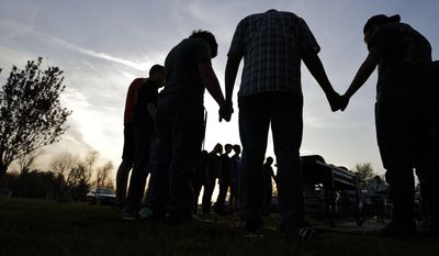 In this Sunday April 10, 2016 photo, youths hold hands for a prayer during a gathering at sunset outside the Christian Fellowship Church in Benton, Ky. (AP Photo/David Goldman)