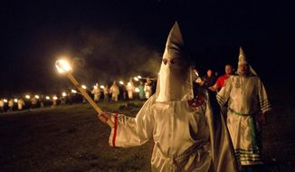 "In this Saturday, April 23, 2016, photo, members of the Ku Klux Klan participate in cross burnings after a ""white pride"" rally in rural Paulding County near Cedar Town, Ga. (AP Photo/John Bazemore)"