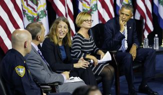 President Barack Obama, right, as Secretary of Health and Human Resources, Sylvia Burwell, center, speaks during an event at the East End Family Resource Center in Charleston, WVa., Wednesday, Oct. 21, 2015. Also attending the event is Charleston police chief, Brent Webster, left, Dr. Michael Brumage, second from left, and Cary Dixon, second from right.  (AP Photo/Steve Helber)