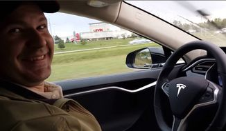 This still image taken from a video published on YouTube on Oct. 15, 2015, shows Joshua Brown of Canton, Ohio, in the driver's seat of his Tesla Model S with no hands on the steering wheel while he demonstrates the car's self-driving mode. Brown was killed on May 7, 2016, in Williston, Fla., when his car hit a tractor-trailer while it was on the Autopilot system. (YouTube via AP)