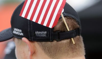 A member of Kasey Kahne's crew displays a U.S. flag in his hat band on pit road before the NASCAR Sprint Cup Series auto race at Daytona International Speedway, Saturday, July 2, 2016, in Daytona Beach, Fla. (AP Photo/John Raoux)