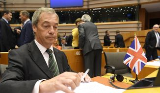 Nigel Farage, the leader of the United Kingdom Independence Party, sits next to a British flag during a special session of European Parliament in Brussels in this June 28, 2016, file photo. Farage announced on Monday, July 4, 2016, that he is resigning as leader of the party. (AP Photo/Geert Vanden Wijngaert, File)