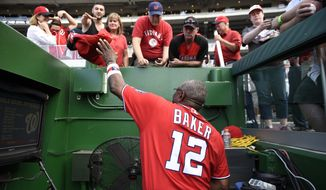 Washington Nationals manager Dusty Baker (12) signs for fans before a baseball game against the Cincinnati Reds, Saturday, July 2, 2016, in Washington. The Reds won 9-4 in ten innings. (AP Photo/Nick Wass) **FILE**