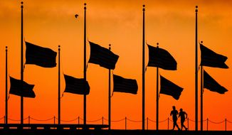 FILE - In this June 13, 2016 file photo, flags fly at half-staff around the Washington Monument at daybreak in Washington, by order of President Obama, the day after more than four dozen people were killed  in the Orlando, Fla., nightclub shootings. As the nation marks Independence Day on Monday, lowering the flag remains a visible, immediate way to pay tribute in hours of tragedy, but flag buffs have noted that the honor has been extended more widely over time, and they and other Americans have questioned whether the country has lowered the bar on the lowering the flag.  (AP Photo/J. David Ake, File)