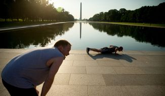 """In this May 25, 2016 photo, members of the running group """"November Project"""" rest after their work out of running up and down the stairs of the Lincoln Memorial, in Washington. Fitness buffs around the country are bringing the 'take the stairs' advice to a whole new level as noteworthy landmarks have become unlikely, yet popular new workout sites. (AP Photo/Andrew Harnik)"""