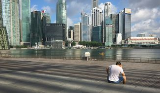 A man talks on his mobile phone in the Marina Bay financial district of Singapore on Tuesday, July 5, 2016. Singapore, which is about the size of New York City, has a population of more than 5 million and its economy relies mainly on finance, tourism and manufacturing. (AP Photo/Wong Maye-E)