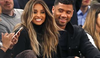 FILE - In this Feb. 9, 2016 file photo, singer Ciara, second from left, and Seattle Seahawks quarterback Russell Wilson sit courtside while attending an NBA basketball game between the New York Knicks and the Washington Wizards in New York. The couple were married Wednesday, July 6, 2016, at Peckforton Castle in Cheshire, England. (AP Photo/Kathy Willens, File)
