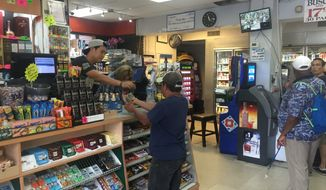 Customers at Tenley Market of Northwest buy lottery tickets, hoping to get rich at one of the luckiest stores in the nation's capital. (by Emma Ann Patton/The Washington Times)