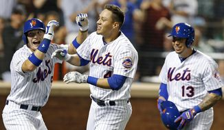 New York Mets left fielder Brandon Nimmo (9), Mets Wilmer Flores (4) and Mets Asdrubal Cabrera celebrate after Nimmo and Cabrera scored on Flores's pinch-hit, three-run, home run during the fifth inning of a baseball game against the Washington Nationals, Thursday, July 7, 2016, in New York. (AP Photo/Kathy Willens)