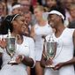Serena Williams, left, and Venus Williams of the U.S hold their trophies after winning the women's doubles final against Yaroslava Shvedova of Kazahkstan and Timea Babos of Hungary on day thirteen of the Wimbledon Tennis Championships in London, Saturday, July 9, 2016. (AP Photo/Tim Ireland)