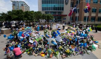 People surround a memorial in honor of the slain Dallas police officers in front of police headquarters, in Dallas, Saturday, July 9, 2016.  A peaceful protest, over the recent shootings of black men by police, turned violent Thursday night as gunman Micah Johnson shot at officers, killing several and injuring others.  (Ting Shen/The Dallas Morning News via AP) MANDATORY CREDIT; MAGS OUT; TV OUT; INTERNET USE BY AP MEMBERS ONLY; NO SALES