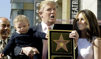 In this Jan. 16, 2007 file photo, Donald Trump, with his wife, Melania Trump, and their son, Barron, pose for a photo after he was honored with a star on the Hollywood Walk of Fame in Los Angeles. (AP Photo/Damian Dovarganes, File)