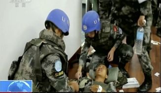 In this image taken from a July 10, 2016, video footage released by China's CCTV via AP Video, Chinese UN peacekeepers tend to a wounded colleague after an attack on an armored personal carrier used by the Chinese peacekeepers in Jebel in South Sudan. Heavy explosions are shaking South Sudan's capital Juba Monday, July 11, 2016, as clashes between government and opposition forces entered their fifth day, witnesses say, pushing the country back toward civil war. (CCTV via AP Video)