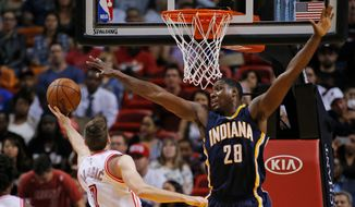 Indiana Pacers Ian Mahinmi (28) blocks the shot by Miami Heat's Goran Dragic (7) during the overtime period of an NBA basketball game, Monday, Feb. 22, 2016, in Miami. The Heat defeated the Pacers 101-93 in overtime. (AP Photo/Joel Auerbach)