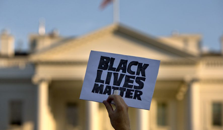 """In this July 8, 2016, photo, a man holds up a sign saying """"black lives matter"""" during a protest of shootings by police, in Washington by the White House. (AP Photo/Jacquelyn Martin) ** FILE **"""