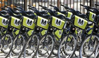 Rows of bikes ready to be shared are lined up in Grand Park near Los Angeles City Hall Thursday, June 7, 2016. The city is rolling out a bicycle sharing program offering bikes for rent from dozens of locations downtown. The agreement with the county's Metropolitan Transportation Authority creates up to 65 bike-sharing stations. Users can pick up a bike from a kiosk, hop on, and then leave it near their destination for someone else to use. (AP Photo/Nick Ut)