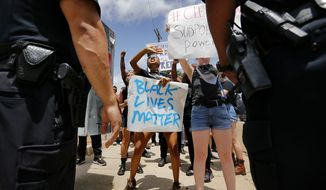 Protesters with the Black Lives Matter movement  argue with police to let them walk down the sidewalk during a rally outside Graceland on Elvis Presley Blvd Tuesday afternoon, July 12, 2016 in Memphis, Tenn.  Dozens of protesters associated with the Black Lives Matter movement demonstrated Tuesday outside the gates of Graceland, the former home of Elvis Presley. Police said four people were detained for blocking the street.  (Mike Brown/The Commercial Appeal via AP)
