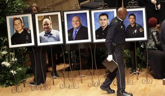 A member of the Dallas Police Choir passes the portraits of five fallen officers prior to a memorial service at the Morton H. Meyerson Symphony Center in Dallas, Tuesday, July 12, 2016. The officers, from left, Michael Krol, Brent Thompson, Lorne Ahrens, Michael Smith and Patrick Zamarripa, were killed and several others injured in a sniper attack in Dallas on Thursday night, July 7. (AP Photo/Eric Gay)