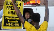 """Melvin Townes, of Baltimore, stands with a """"Justice 4 Freddie Gray"""" sign in front of a police officer during a protest Friday, July 8, 2016, in Baltimore. (Caitlin Few/The Baltimore Sun via AP)"""