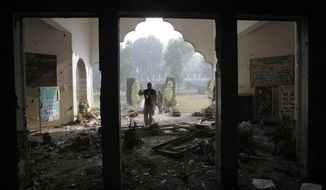 FILE -- In this Dec. 17, 2014 file photo, a Pakistan army soldier inspects the Army Public School that was  attacked a day before by Taliban gunmen, in Peshawar, Pakistan. The Pakistani army said Wednesday, July 13, 2016 that the mastermind of the 2014 attack on an army-run school has been killed in a U.S. drone strike. A Pakistani military spokesman says that a U.S. Army general confirmed the death of Taliban leader Khalifa Umar Mansoor in a phone call to Pakistans army chief. (AP Photo/B.K. Bangash, File)