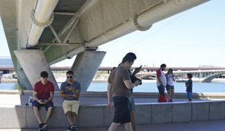 In this Tuesday, July 12, 2016, photo, Pokemon Go players look for Pokemon at Tempe Beach Park in Tempe, Ariz. The park is a popular location for players. (AP Photo/Beatriz Costa-Lima)