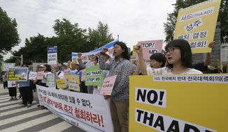 "Protesters shout slogans during a rally to denounce deploying the Terminal High-Altitude Area Defense, or THAAD, in front of the Defense Ministry in Seoul, South Korea, Wednesday, July 13, 2016. The site in South Korea that will be the base for an advanced U.S. missile defense system that the government says is designed to cope with North Korean threats will be announced Wednesday, Seoul officials said. The banner in the center reads: ""Oppose deploying the THAAD."" (AP Photo/Ahn Young-joon)"