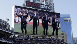 In this Tuesday, July 12, 2016, photo, The Tenors, shown on the scoreboard, perform during the Canadian National Anthem prior to the MLB baseball All-Star Game, in San Diego. A member of a Canadian singing quartet changed a lyric in his country's national anthem and held up a sign proclaiming 'All Lives Matter' during a pregame performance at the 87th All-Star Game on Tuesday. The Tenors, a group based in British Columbia, caused a stir at Petco Park with Remigio Pereira's actions while singing 'O Canada' (AP Photo/Gregory Bull, File) **FILE**