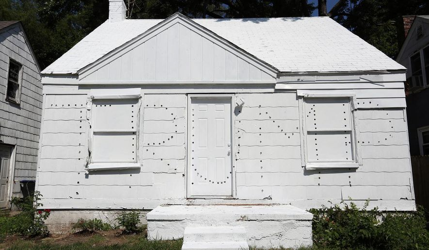 This photo taken July 12, 2016, shows a new project by Ryan Mendoza, an artist previously known for using an abandoned Detroit home for art, who has built a new project using two abandoned homes on either side of an occupied home. The artist has taken the homes that sit empty and has painted them white and then punched holes in the homes to spell Trump on one and Clinton on the other. At night the lights that he installed into the holes illuminate and the message he wants to convey is that there is a lack of political choice with Clinton and Trump. In addition, this signifies the state of America in the middle of this political campaign. (Regina H. Boone/Detroit Free Press via AP)