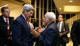 In this Jan. 16, 2016, file pool photo, Secretary of State John Kerry talks with Iranian Foreign Minister Mohammad Javad Zarif in Vienna, after the International Atomic Energy Agency (IAEA) verified that Iran has met all conditions under the nuclear deal. (Kevin Lamarque/Pool via AP, File)