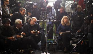 Reporters and photographer wait for comment from Republican congressmen who are meeting with President Obama regarding the government shutdown and debt ceiling at the West Wing at the White House in Washington on Oct. 10, 2013. (Associated Press) **FILE**