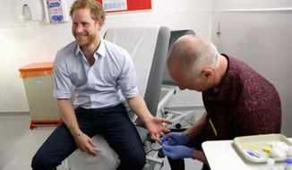 Britain's Prince Harry has blood taken for an HIV test, administered by Specialist Psychotherapist Robert Palmer during a visit to highlight the fight against HIV and AIDS, at the Burrell Street Sexual Health Centre in Southwark, London, Thursday, July 14, 2016. (Chris Jackson/PA via AP)