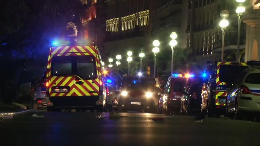 Ambulances and police cars are seen after a truck drove on to the sidewalk and plowed through a crowd of revelers who had gathered to watch Bastille Day fireworks in the French resort city of Nice. (BFMTV via Associated Press)