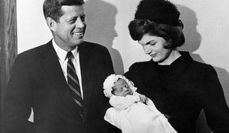 In this Dec. 8, 1960 photo, President John F. Kennedy and first lady Jacqueline Kennedy pose at Georgetown University Hospital in Washington with their son, John F. Kennedy Jr., following a baptism for the infant. The younger Kennedy was born Nov. 25. A documentary film on John Kennedy Jr.'s life opens Friday, July 22, 2016, in select theaters. (AP Photo, File)