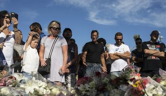 People stand near a makeshift memorial for the victims killed in an attack where a truck mowed through revelers in Nice, southern France, Friday, July 15, 2016. A large truck mowed through revelers gathered for Bastille Day fireworks in Nice, killing more than 80 people and sending people fleeing into the sea as it bore down for more than a mile along the Riviera city's famed waterfront promenade. (AP Photo/Laurent Cipriani)