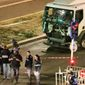 Police investigate the scene after a truck plowed through Bastille Day revelers in the French resort city of Nice, France, Thursday, July 14, 2016. France was ravaged by its third attack in two years when a large white truck mowed through revelers gathered for Bastille Day fireworks in Nice, killing at dozens of people as it bore down on the crowd for more than a mile along the Riviera city's famed seaside promenade. (Sasha Goldsmith via AP)