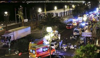 Emergency services vehicles work on the scene after a truck, left, plowed through Bastille Day revelers in the French resort city of Nice, France, Thursday, July 14, 2016. (Sasha Goldsmith via AP)