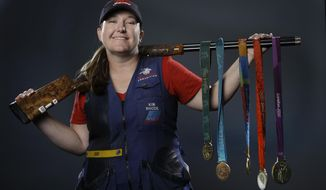 In this March 8, 2016, file photo, double trap and skeet shooter Kim Rhode poses for photos with her Olympic medals at the 2016 Team USA media summit in Beverly Hills, Calif. (AP Photo/Jae C. Hong, File)