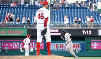 The Pittsburgh Pirates' Starling Marte rounds the bases after he hit a home run as Washington Nationals relief pitcher Oliver Perez looks on during the 18th inning on Sunday. The Pirates won 2-1 in 18 innings to avoid a three-game sweep by the Nationals. (Associated Press)