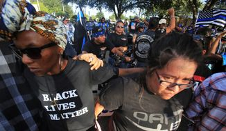 Supporters of the Blue Lives Matter movement, back, stand as supporters of the Black Live Matter hold a rally at McAllen City Hall in McAllen, Texas, Saturday, July 16, 2016. (Joel Martinez/The Monitor via AP) ** FILE **