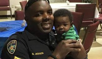 """In a post accompanied by his holding his newborn son, Baton Rouge Police Officer Montrell Jackson described himself as """"tired physically and emotionally"""" but swore he'd not give in. (Associated Press)"""