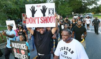 Mario Hicks, middle, holds a sign as he chants and marches during a Black Lives Matter march and rally in Sanford, Fla., Sunday, July 17, 2016. Sanford police chief Cecil Smith is pictured in the background at far right. (Stephen M. Dowell/Orlando Sentinel via AP)