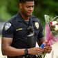 Baton Rouge Police Officer Markell Morris holds a bouquet of flowers and a Superman action figure that a citizen left at the Our Lady of the Lake Hospital where the wounded police officers were brought after the shooting Sunday morning. (The Times via Associated Press)