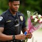 Baton Rouge Police Department Officer Markell Morris holds a bouquet of flowers and a Superman action figure that a citizen left at Our Lady of the Lake Hospital, where wounded police officers were brought after Sunday morning's shootings. (The Times via Associated Press)