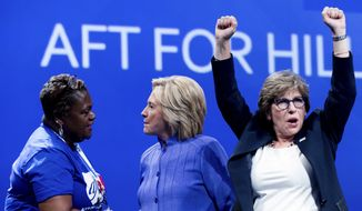 Democratic presidential candidate Hillary Clinton, center, greets a supporter on stage with AFT President Randi Weingarten, right, after speaking at the American Federation of Teachers convention at the Minneapolis Convention Center in Minneapolis, Monday, July 18, 2016. (AP Photo/Andrew Harnik)