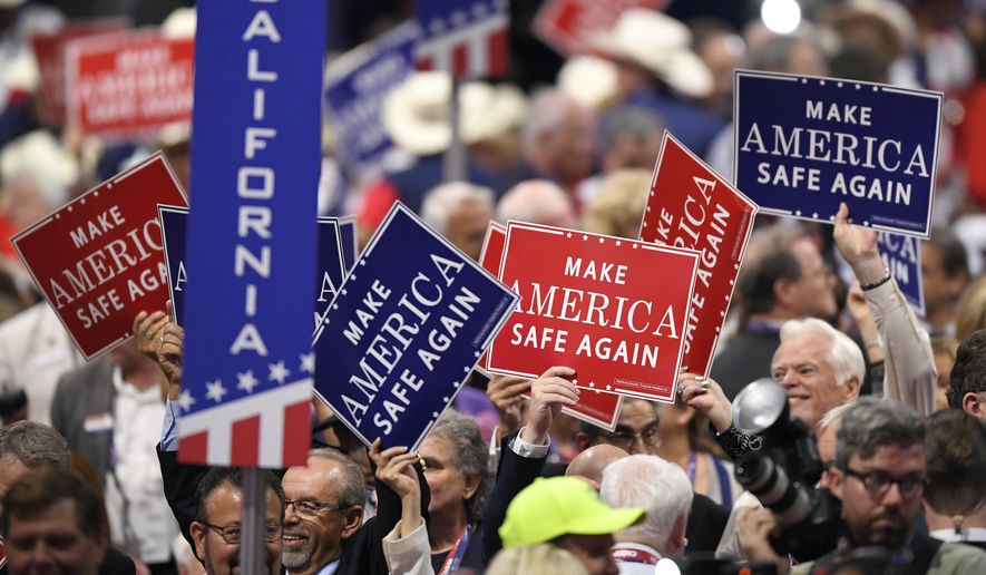 Signs are passed out to delegates during the evening session of the opening day of the Republican National Convention on Monday in Cleveland. (Associated Press)