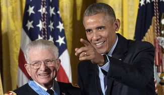 President Barack Obama points after presenting the Medal of Honor to retired Lt. Col. Charles Kettles of Michigan during a ceremony in the East Room of the White House in Washington, Monday, July 18, 2016. Kettles distinguished himself in combat operations near Duc Pho, Vietnam, and is credited with saving the lives of 40 soldiers and four of his own crew members. (AP Photo/Susan Walsh)