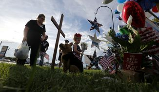 Allie Allen and her daughter Harper, 3, place stuffed animals and flowers at a makeshift memorial at the scene of the shooting of police officers, in Baton Rouge, Monday, July 18, 2016. Multiple police officers were killed and wounded Sunday morning in a shooting near a gas station in Baton Rouge, less than two weeks after a black man was shot and killed by police here, sparking nightly protests across the city. (AP Photo/Gerald Herbert)